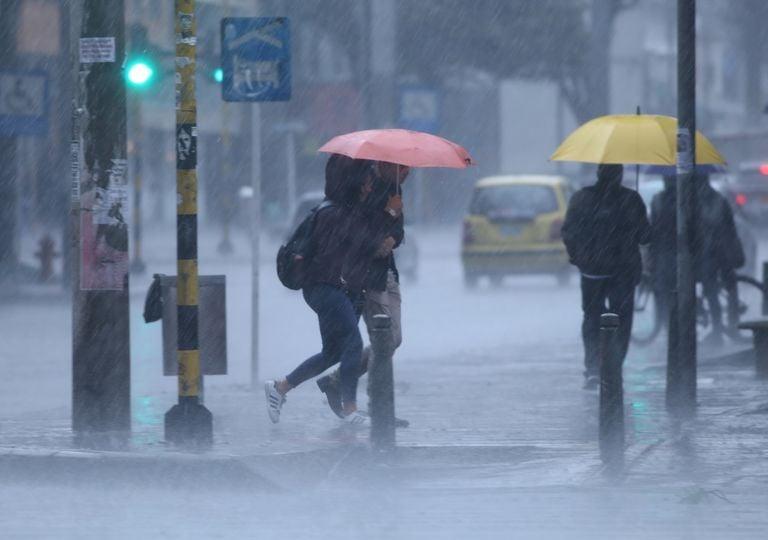 Personas con paraguas caminando bajo la lluvia, calles inundadas
