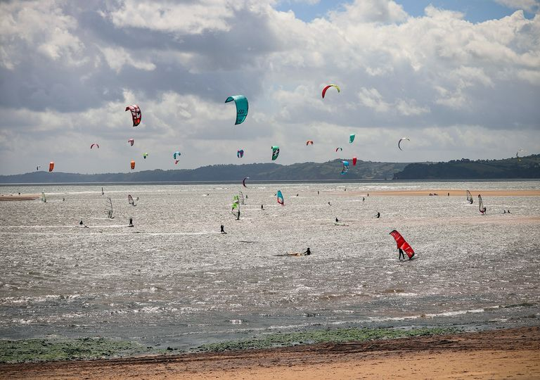 Cloudy, windy beach with windsurfers.