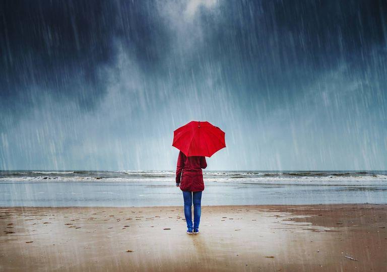 tempestade; chuva; mar; mulher; guarda-chuva;