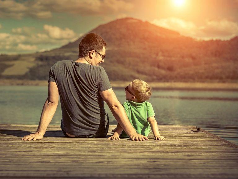 hijo y padre sentados cerca del lago