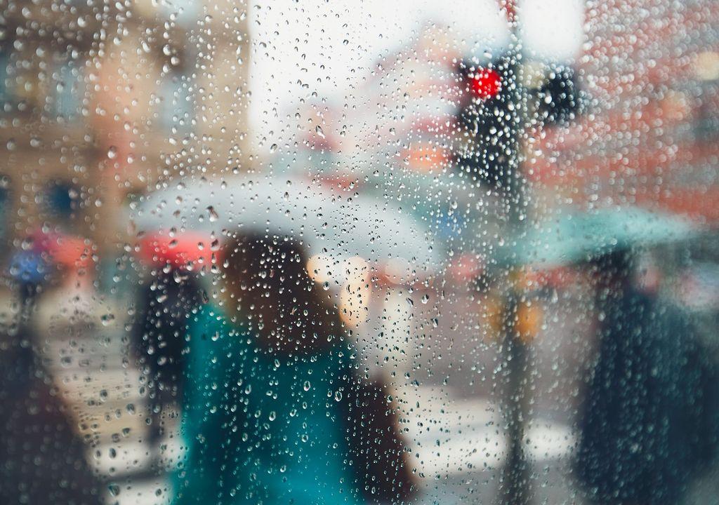personas cruzando el semáforo en día de lluvia