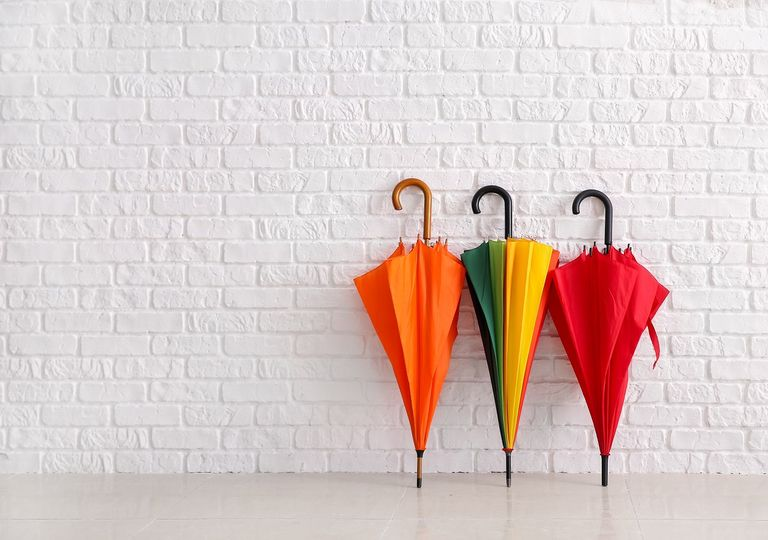 paraguas coloridos apoyados en una pared blanca